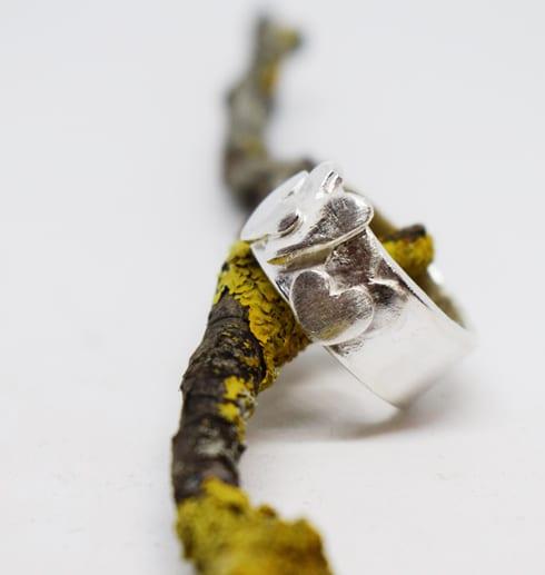 bred silverring på trädgren med vit botten