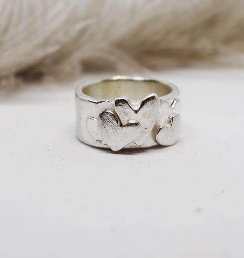 bred silverring med hjärtan på vit botten med fjäder i bakgrunden