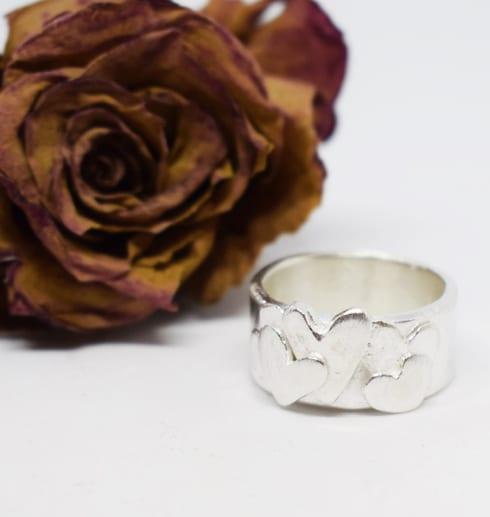 silverring med hjärtan på vit botten med rostfärgad ros bakom