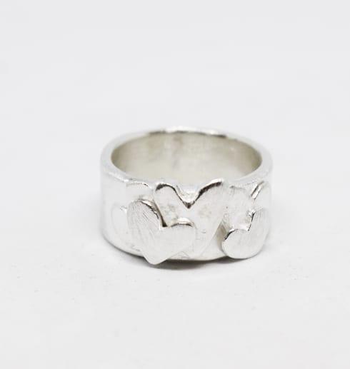 silverring med hjärtan mot vit bakgrund