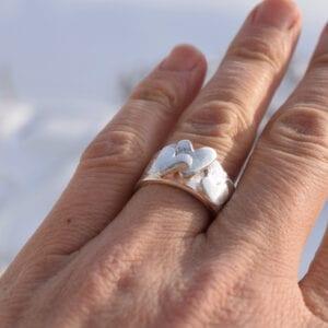 bred silverring med hjärtan på ringer utomhus