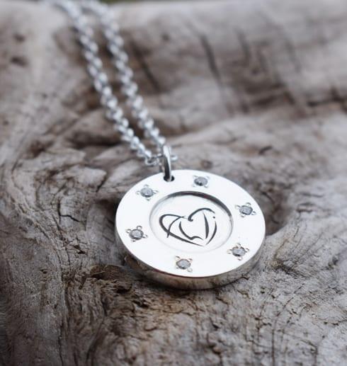 silverhalsband med stenar och logga på trädbit