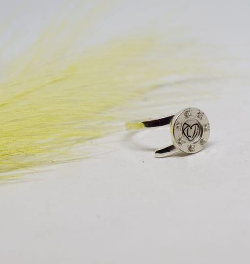 silverring på vit bakgrund med gul fjäder bredvid