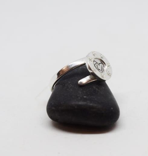 silverring som är ställbar på svart sten med vit bakgrund