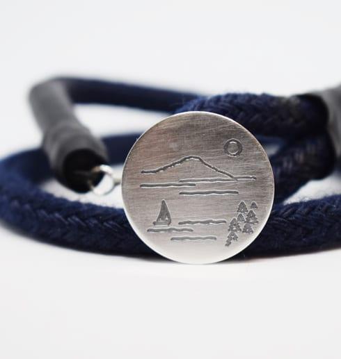 marinblått armband med silverbricka mot vit bakgrund