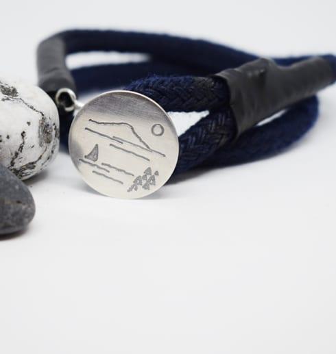 Marinblått armband med silverbricka på vit botten med stenar bredvid
