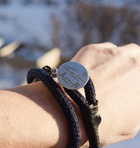 marinblått armband med silverbricka på handled utomhus