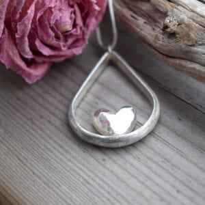 droppformat silverhalsband med hjärta i mitten på trä med en ros bredvid utomhus