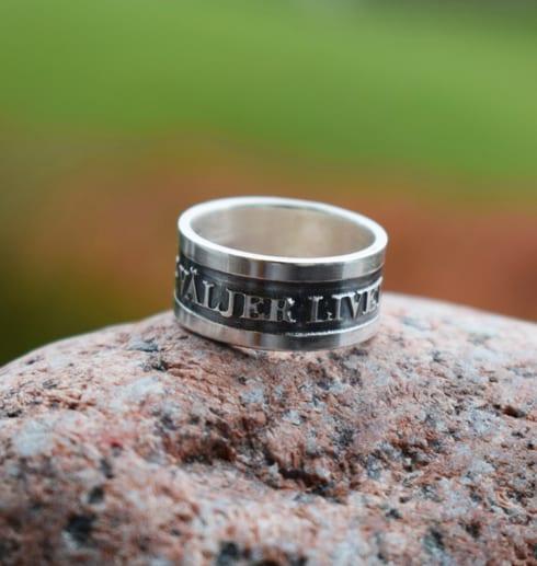 jag väljer livet stpr det på denna silverring som är fotad utomhus på en röd sten