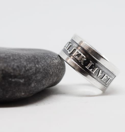 silverring med text mot grå sten och vit bakgrund