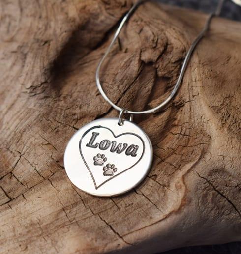 silversmycke med hjärta och tassar på trädbit