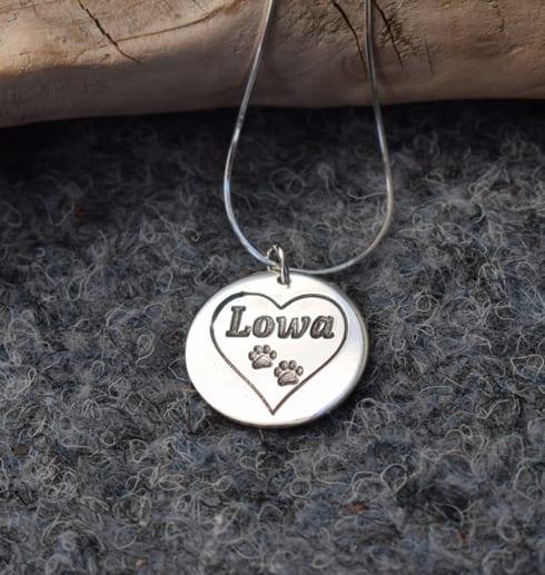 silverhalsband med hjärta och tassar på grå botten