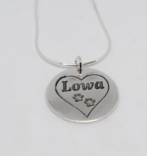 silverhalsband med hjärta och hundtassar på vit bakgrund