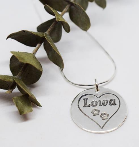 silversmycke med hjärta och tassar på vit botten med grön kvist