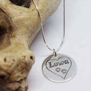 silverhalsband med hjärta och tassar med en trädgren