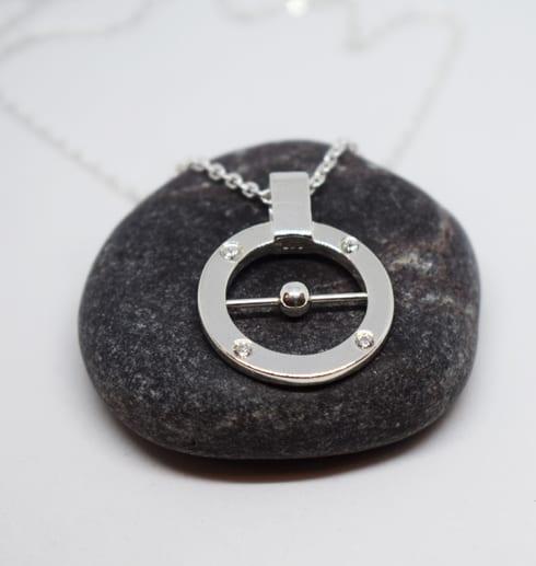 runt silverhalsband på mörkgrå sten med vit bakgrund