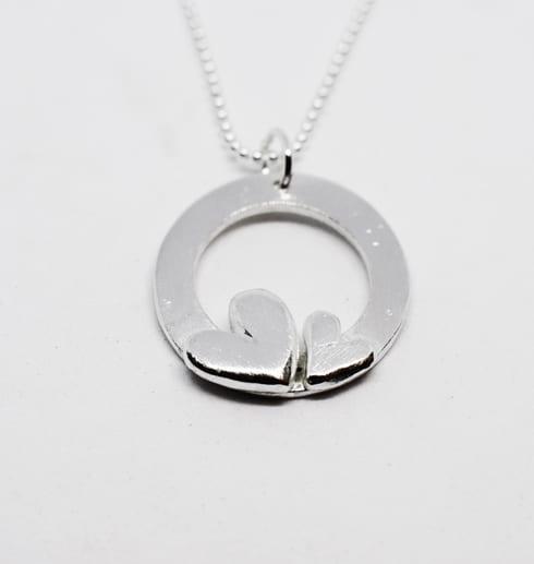silverhänge med två hjärtan i kedja mot vit bakgrund