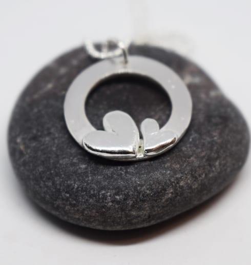 silversmycke med två hjärtan på en mörkgrå sten