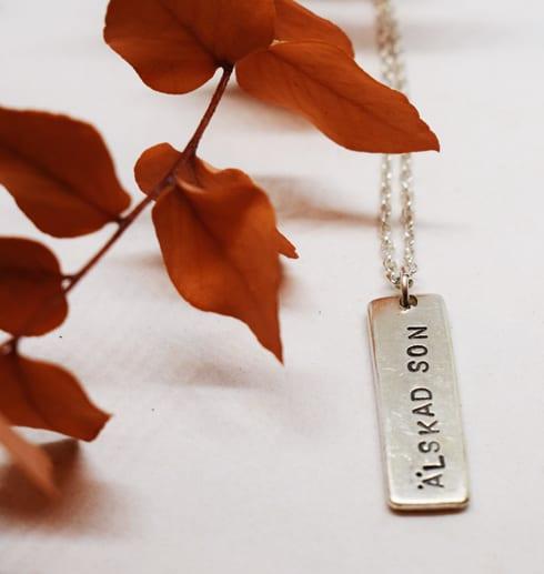 smycke med texten älskad son mot vit bakgrund och orange kvist