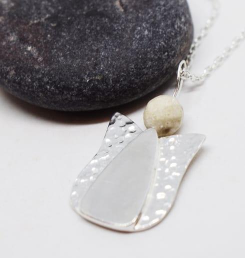 ängel i silver med mörkgrå sten bakom