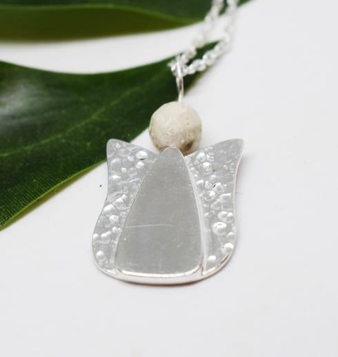 ängel i silver med grönt blad bredvid