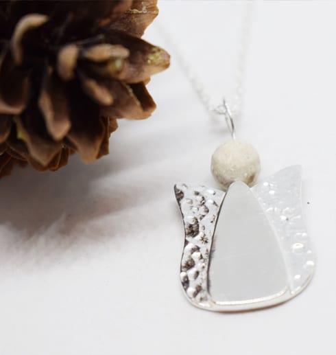ängel i silver med kotte bredvid