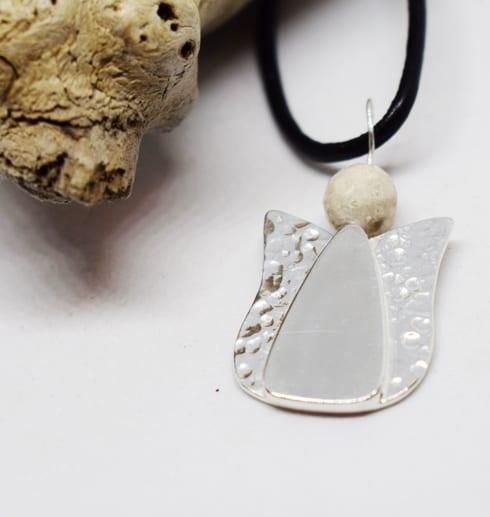 ängel i silver med svart läderrem och trädgren bredvid