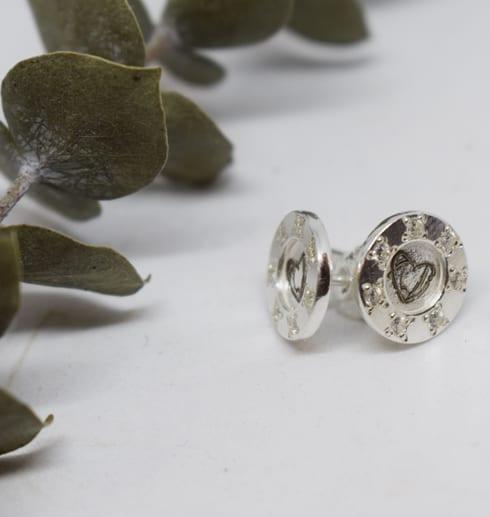 silverörhängen på vit bakgrund med grön kvist