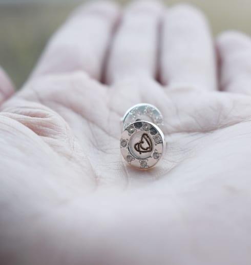 silverörhängen på handflata
