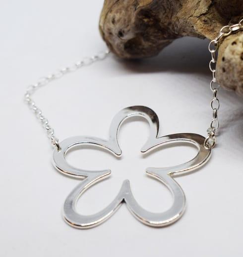 silverhalsband i form av en blomma på vit bakgrund med trädgren
