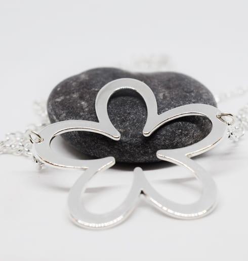 silverblomma ett fint halsband på grå sten med vit bakgrund