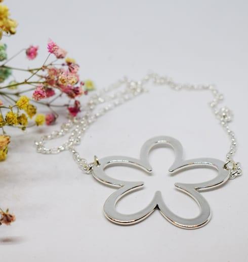 silverhalsband i form av en stor blomma på vit bakgrund med små blommor i rosa och gult