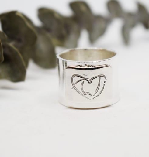 bred silverring med vit bakgrund och grön kvist bakom