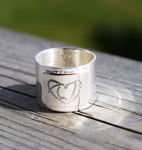 bred silverring med ALTIs logga på trä utomhus