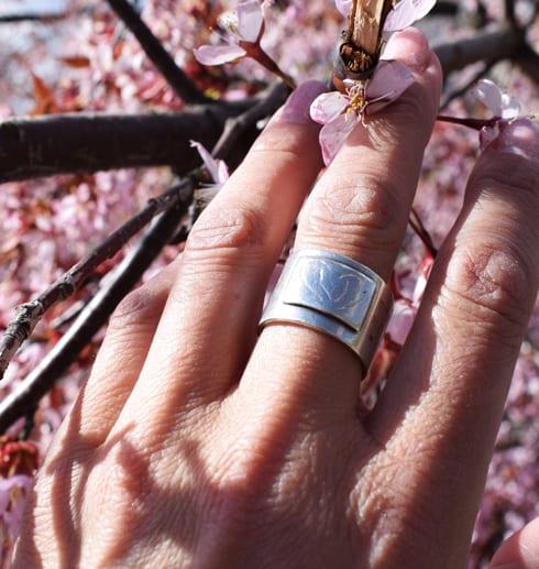 bred silverring på finger med rosa blommor bakom utomhus