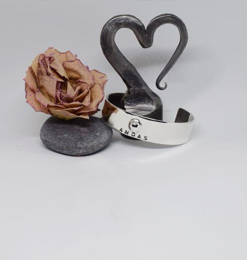 silverarmband med järnhjära och ros bakom