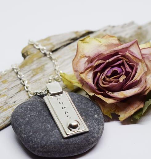 silverhalsband med texten ANDAS på sten med trä och ros bakom