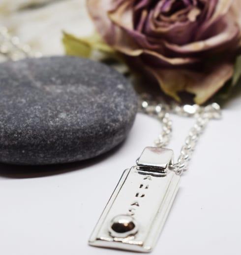 andas halsband i silver med ros och sten bredvid