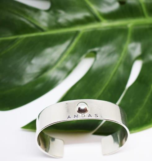silverarmband med grönt blad bakom
