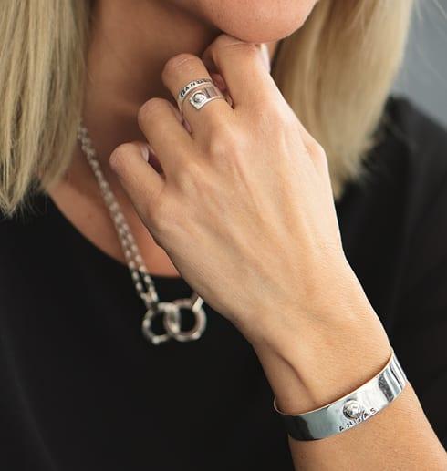 kvinna med armband, halsband och ring i silver