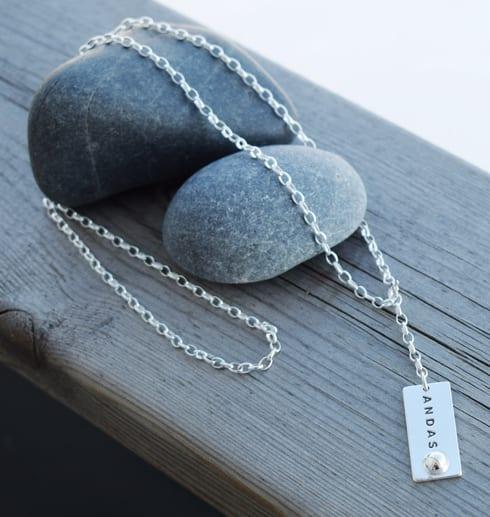 Halsband med texten ANDAS över stenar på trä utomhus