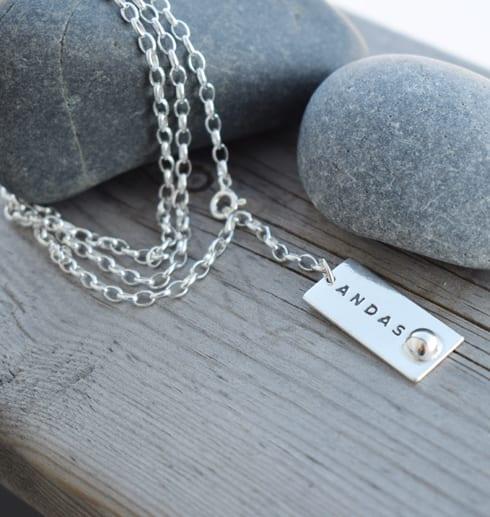 Silversmycke med texten NDAS på stenar mot trä utomhus