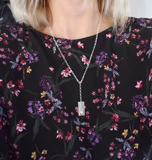 kvinna med blommig blus med silverhalsband med texten ANDAS