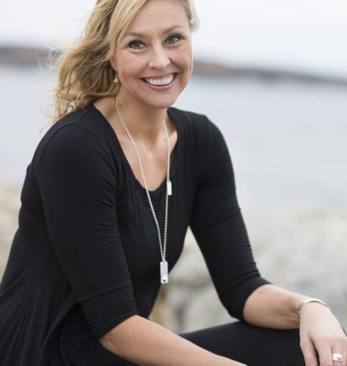 kvinna på klippa vid havet med silverhalsband runt halsen