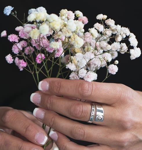 silverring med texten ANDAS på finger på kvinna med en bukett blommor i rosa, gult och vitt