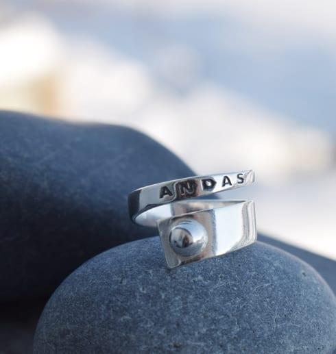 silverring med texten ANDAS på grå stenar utomhus