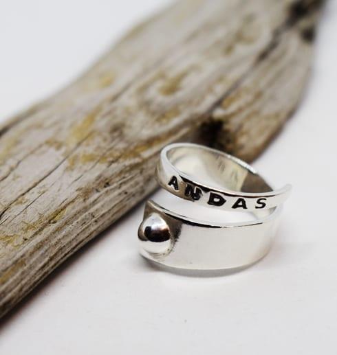 Silverring med texten ANDAS motvit bakgrund med treädbit bredvid