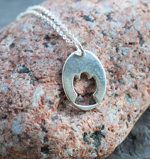 halsband i form av en ängel mot en röd sten