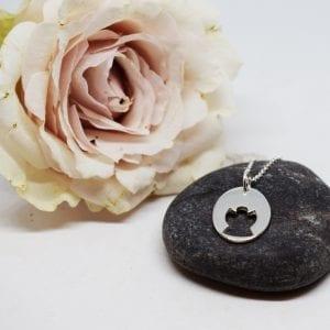 silverhalsband med en ängel på en grå sten med en rosa ros bredvid