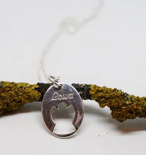 silverhalsband i form av en ängel mot en trädgren med vit bakgrund